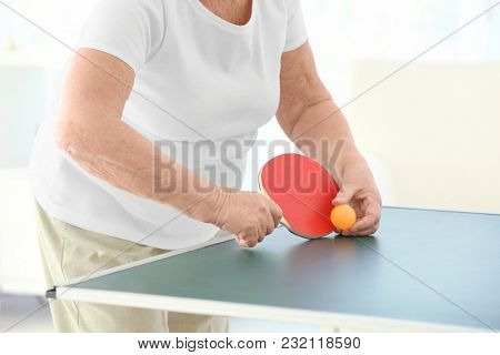 Senior woman playing table tennis indoors