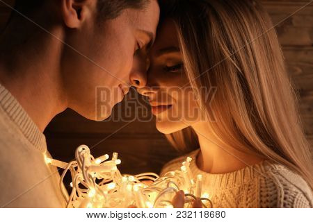 Portrait of young loving couple with fairy lights, closeup