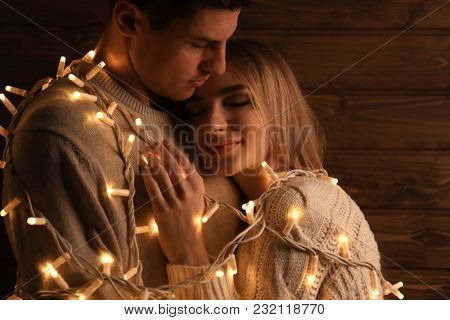 Young loving couple with fairy lights on wooden background