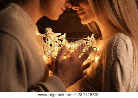Young loving couple with fairy lights, closeup