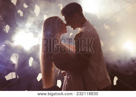 Young loving couple on dark background with backlit and smoke