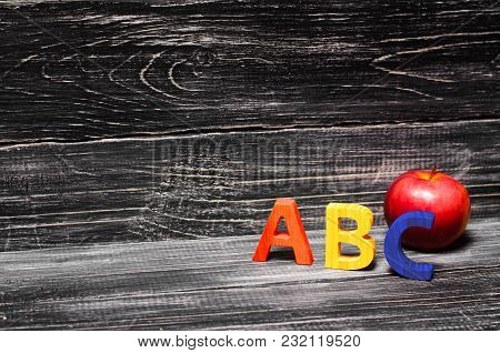 Alphabet Letters And Red Apple On A Black Background. The Concept Of Education, Knowledge And Scienc