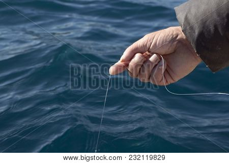 Man With Fishing Line In His Hand Catching Fish From The Side Of The Boat