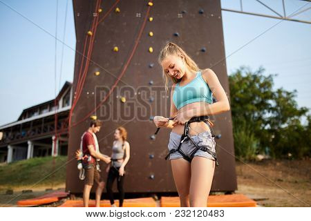 Pretty Caucasian Woman Puts On Belaying Harness For Practice On Artificial Rock Wall. Slim Strong He