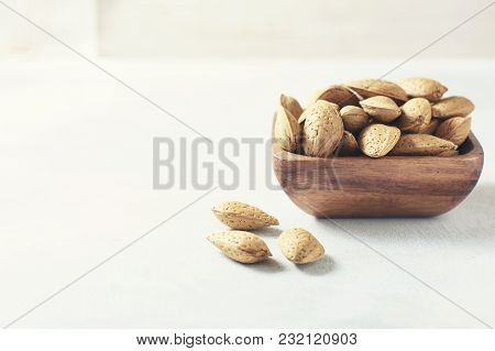 Raw Almond In The Sinks In A Wooden Bowl On A White Background, Selective Focus. The Concept Of Heal