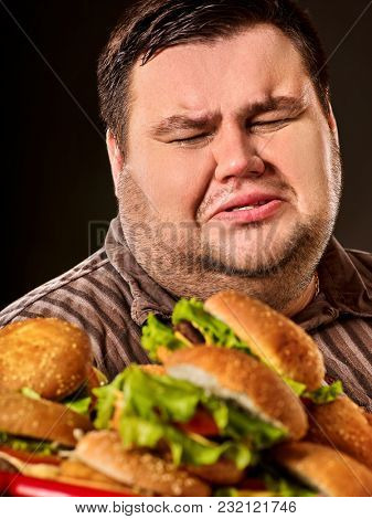 Fat man eating fast food hamberger. Breakfast for overweight person. Junk meal leads to obesity. Person regularly overeats concept on black background. Feast on the occasion of the feast.