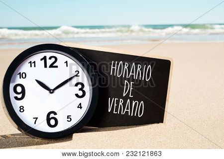 closeup of a clock and a signboard with the text horario de verano, summer time written in spanish, on the sand of a beach