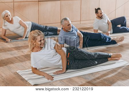 Smiling Senior People Training On Yoga Mats At Training Class