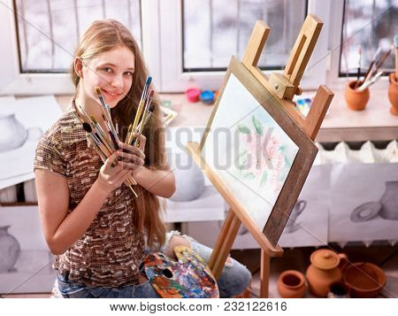 Artist painting on easel in studio. Authentic girl paints with brush in morning light toning. Competition on drawing. Best choice of brushes for watercolor painting. How to choose right brush.