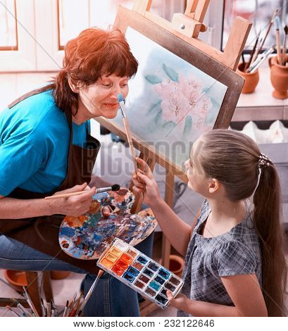 Artist painting easel in studio. Authentic old woman and kids girl paints with palette watercolor paints palette and brush morning sunlight. Private business drawing. Granddaughter helps grandmother.
