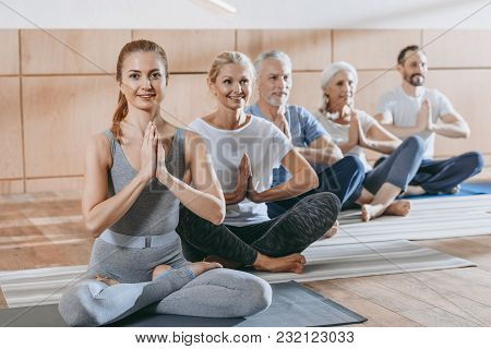 Senior People With Instructor Sitting In Lotus Position On Yoga Mats