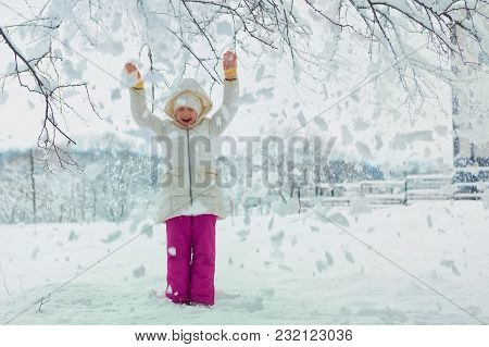 Little Girl On A Winter Day. Snow From The Tree Falls On It