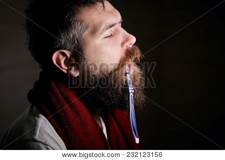 Sleepy Bearded Man Brushing Teeth With A Toothbrush In Front Of The Bathroom Mirror In Morning. Man