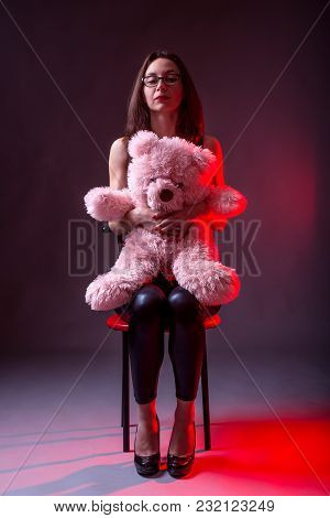 Young Woman Sitting On A Chair And Holding A Pink Bear.
