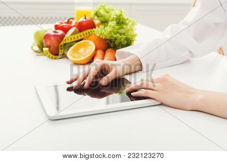Closeup Of Female Nutritionist Hands Working On Digital Tablet In Office. Woman Dietitian Typing, Co