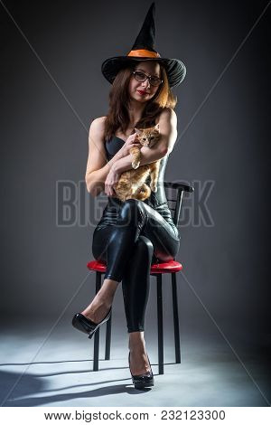 Woman In Witch Costume Sitting On A Chair And Holding A Kitten, Background Halloween.