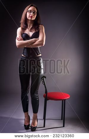 Sexy Young Woman In Corset And Latex Pants Posing Near A Chair On A Gray Background.