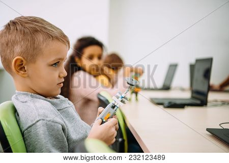 Side View Of Serious Little Kid With Diy Robot