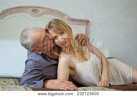 Beautiful Young Woman With Her Senior Lover Lying On The Bed. Man Kissing His Girlfriend.portrait Of