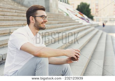 Closeup Of Smiling Businessman In Eyeglasses Drinking Coffee While Sitting On Stone Stairs, Copy Spa