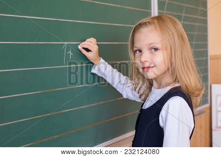 A Small Beauty Of A First Grade Student At A School Near The Board Solves The Problem. Emotions Of S