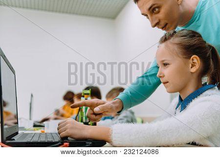 Schoolgirl Working With Teacher On Her Robot Education Project