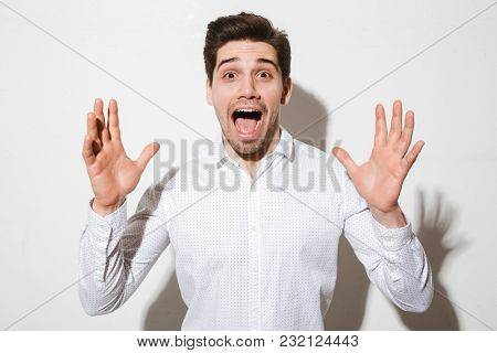 Portrait of a surprised young man dressed in shirt screaming over white wall background with a shadow