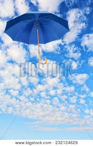 Mary Poppins Umbrella.blue Umbrella Flies In Sky Against Of White Clouds.wind Of Change Concept.
