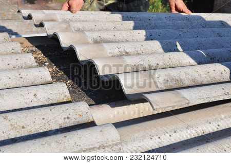 Asbestos removal. Roofer replace damaged asbestos tile. Roofing construction. poster