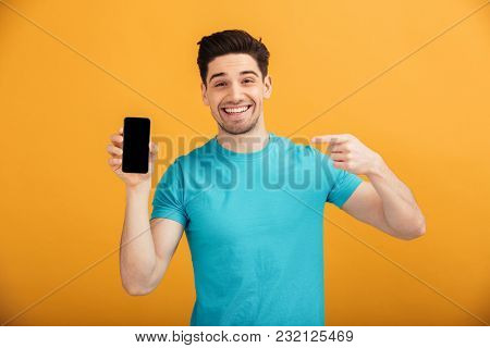 Portrait of a smiling young man in t-shirt pointing finger at blank screen mobile phone isolated over yellow background