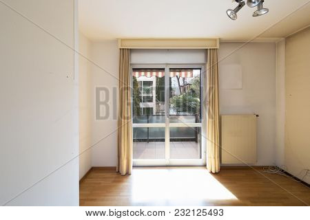 White empty room with window and parquet. Room to be renovated. Nobody inside