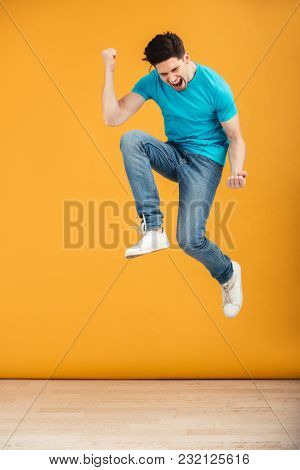 Full length portrait of a joyful young man jumping while celebrating over yellow background