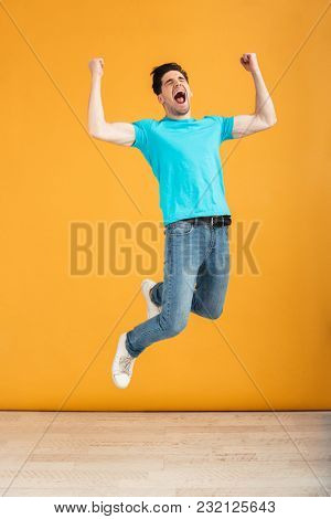 Full length portrait of a cheerful young man jumping while celebrating over yellow background