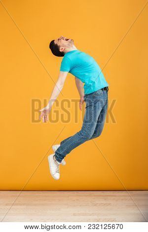 Full length portrait of a satisfied young man jumping while celebrating over yellow background