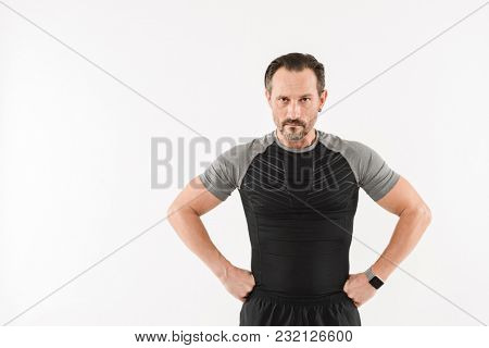 Image of athletic man 30s wearing sportswear looking on camera with concentrated strict gaze while resting after doing sports isolated over white background