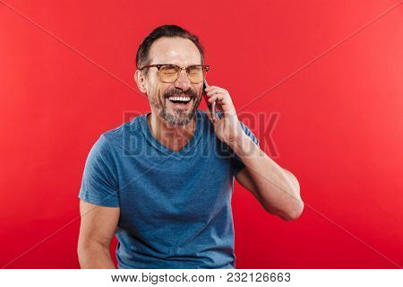 Portrait of happy brunette man having pleasant mobile conversation and speaking on smartphone in studio isolated over red background