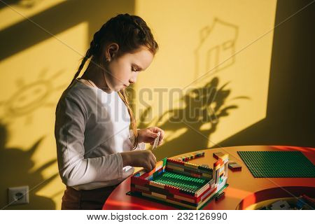 Focused Little Child Building House With Constructor
