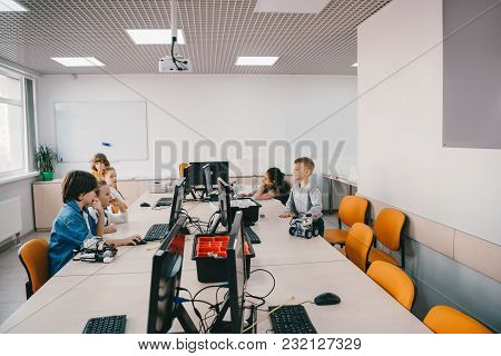 Group Of Kids Working With Computers On Machinery Class