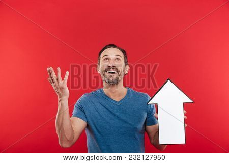 Photo of pleased guy 30s holding blank speech arrow pointer directing upward on copy space isolated over red background