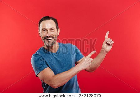 Cheerful emotions of unshaved man 30s in casual blue t-shirt smiling and pointing fingers upward on copyspace closeup isolated over red background