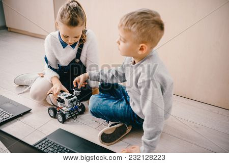 Schoolkids Sitting On Floor With Diy Robot And Laptop