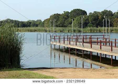 Quiet Fishing Pier At Lake In Summer