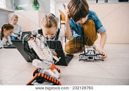 Concentrated Kids Sitting On Floor At Machinery Class, Stem Education Concept