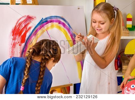 Children painting finger on easel. Group of kids girl and boy with teacher learn paint in class school. Child picture on background. Students draw rainbow. Quiet environment for creativity.