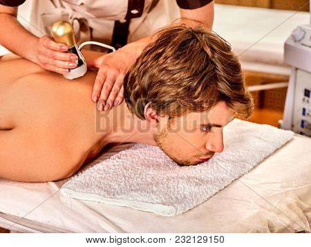 Man back massage beauty salon. Electric stimulation man skin care. Professional equipment microcurrent body lift. Improvement of skin condition. Man receiving electroporation skin care therapy.