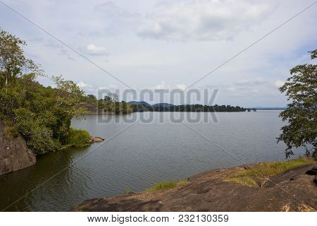 Picturesque Sri Lankan Sorabora Lake With Rocky Banks And Wooded Hills Overlooking Rippled Water Und