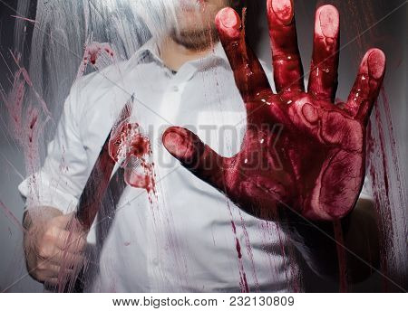Killer With Bloody Sharp Big Knife Touching A Glass With Bloody Hand.