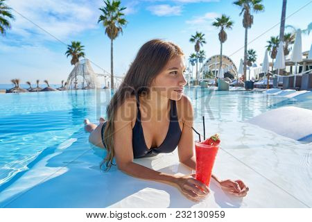 beautiful woman on infinity pool drinking cocktails at resort on the beach