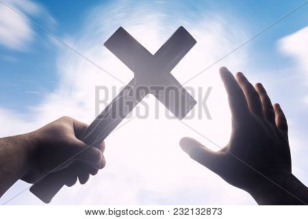 First Person View Photo Of A Male Hands Holding A Cross On A Bright Light Shine With Blue Skies Back