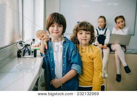 Happy Little Kids With Diy Robot Embracing On Machinery Class